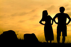 Couples heureux sur la roche de coucher du soleil - silhouette Photographie stock