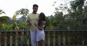 Couples heureux sur la terrasse embrassant parler au-dessus du paysage de coucher du soleil, du jeune homme divers et de la femme banque de vidéos