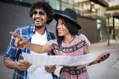 Couples heureux sur la ville guid?e de vacances avec la carte image libre de droits