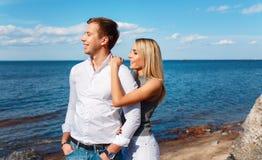Couples heureux sur le fond de mer Jeunes couples heureux riant et étreignant sur la plage Images libres de droits
