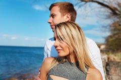Couples heureux sur le fond de mer Jeunes couples heureux riant et étreignant sur la plage Images stock
