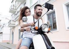 Couples heureux sur le scooter rendant le selfie sur le smartphone extérieur Photo libre de droits