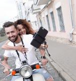 Couples heureux sur le scooter rendant le selfie sur le smartphone extérieur Images stock