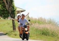 Couples heureux sur un scooter Image libre de droits