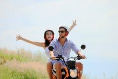 Couples heureux sur un scooter Images stock