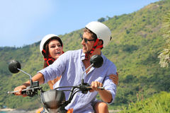 Couples heureux sur un scooter Photos stock