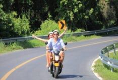 Couples heureux sur un scooter Photographie stock libre de droits