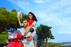Couples heureux sur un scooter aux vacances d'été Images stock