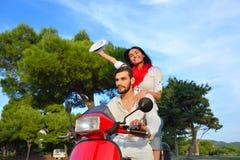 Couples heureux sur un scooter aux vacances d'été Photos libres de droits