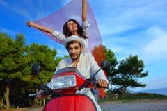 Couples heureux sur un scooter aux vacances d'été Image libre de droits