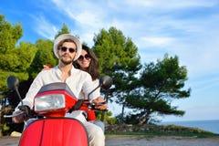 Couples heureux sur un scooter aux vacances d'été Photographie stock libre de droits