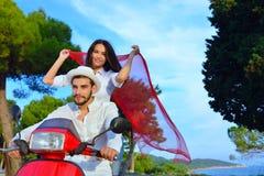 Couples heureux sur un scooter aux vacances d'été Photos stock