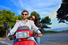 Couples heureux sur un scooter aux vacances d'été Image stock