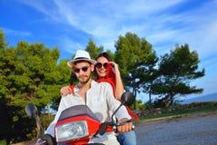 Couples heureux sur un scooter aux vacances d'été Photo libre de droits