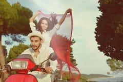 Couples heureux sur un scooter aux vacances d'été Photographie stock