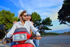 Couples heureux sur un scooter aux vacances d'été Photo stock
