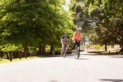 Couples heureux sur un tour de vélo Photos libres de droits