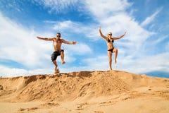 Couples heureux sur une plage sur un fond de ciel bleu et de nuages Photographie stock