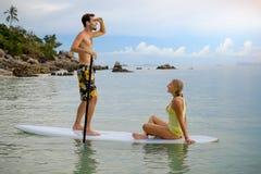 Couples heureux surfant ensemble sur le panneau de palette au coucher du soleil Images libres de droits