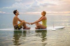Couples heureux surfant ensemble sur le panneau de palette au coucher du soleil Photographie stock libre de droits