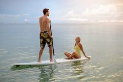 Couples heureux surfant ensemble sur le panneau de palette au coucher du soleil Photo libre de droits