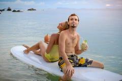 Couples heureux surfant ensemble sur le panneau de palette au coucher du soleil Image libre de droits