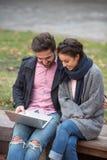 Couples heureux surfant l'Internet dans la ville Photos stock