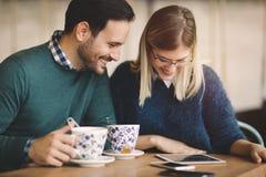 Couples heureux surfant sur le comprimé Images stock