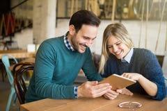 Couples heureux surfant sur le comprimé Image stock