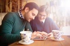 Couples heureux surfant sur le comprimé Photographie stock libre de droits