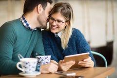 Couples heureux surfant sur le comprimé Photo libre de droits