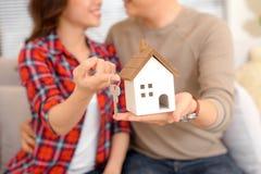 Couples heureux tenant des clés sur la nouvelle miniature de maison et de maison - vraie image libre de droits