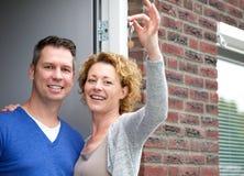 Couples heureux tenant des clés sur leur nouvelle maison photographie stock