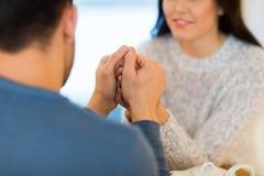 Couples heureux tenant des mains au restaurant ou au café Images stock