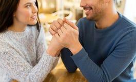 Couples heureux tenant des mains au restaurant ou au café Photos stock