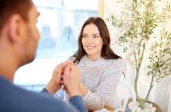 Couples heureux tenant des mains au restaurant ou au café Photo stock