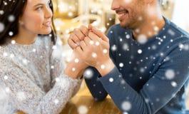 Couples heureux tenant des mains au restaurant ou au café Photo libre de droits