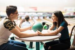 Couples heureux tenant des mains au Tableau dans le club de bowling Photo libre de droits