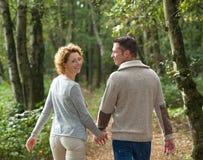 Couples heureux tenant des mains et marchant dans la forêt photos stock
