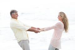 Couples heureux tenant des mains et souriant à l'un l'autre Image stock