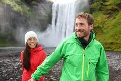 Couples heureux tenant des mains par la cascade dehors Photos libres de droits