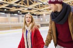 Couples heureux tenant des mains sur la piste de patinage Photographie stock libre de droits
