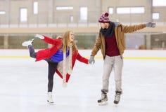 Couples heureux tenant des mains sur la piste de patinage Image stock