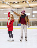 Couples heureux tenant des mains sur la piste de patinage Images stock