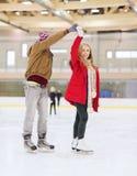 Couples heureux tenant des mains sur la piste de patinage Images libres de droits