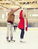 Couples heureux tenant des mains sur la piste de patinage Image libre de droits