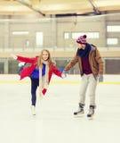 Couples heureux tenant des mains sur la piste de patinage Photos libres de droits