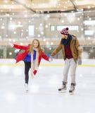 Couples heureux tenant des mains sur la piste de patinage Photo libre de droits