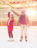 Couples heureux tenant des mains sur la piste de patinage Photos stock