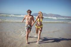 Couples heureux tenant des mains tout en courant sur le rivage Photos libres de droits
